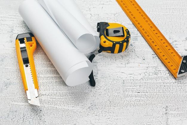Cianografie architettoniche e rotoli di cianografia e strumenti di disegno sul piano di lavoro.