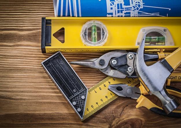 Cianografie blu, livello di costruzione, quadrato di prova, artiglio, martello, pinze e tagli di stagno su tavola di legno