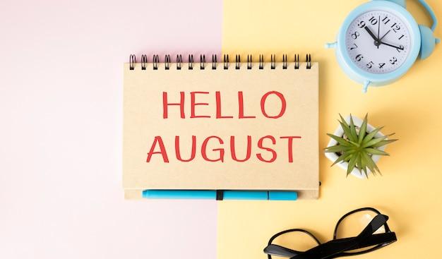 Ciao agosto - testo su un taccuino su un brillante giallo-rosa