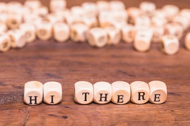 Ciao, concetto fatto con cubetti a forma di blocco sulla scrivania in legno