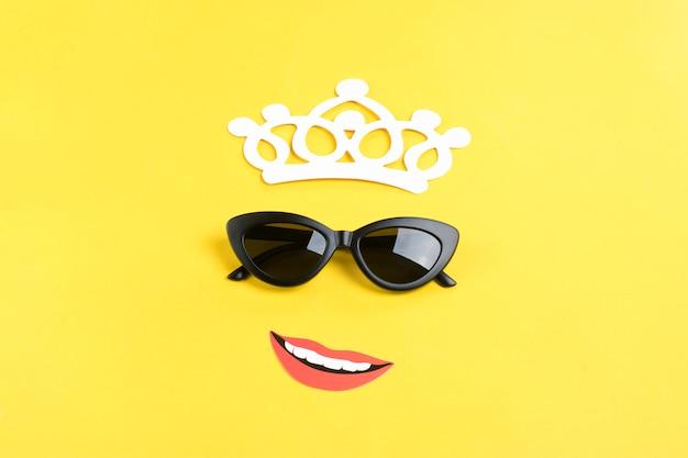 Ciao estate il sole con eleganti occhiali da sole neri, corona, bocca sorridente sul giallo