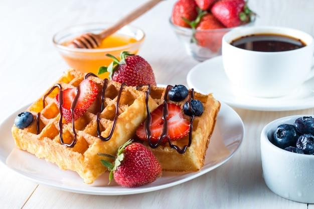 Cibi freschi fatti in casa di waffle belgi ai frutti di bosco con miele, cioccolato, fragola, mirtillo, sciroppo d'acero e crema. concetto sano della prima colazione del dessert con succo