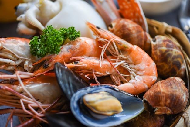 Cibo a vapore cotto servito concetto di buffet di frutti di mare - gamberetti freschi gamberi calamari cozze maculato babilonia crostacei granchio e salsa di frutti di mare limone su sfondo piatto