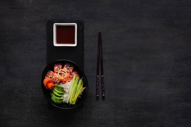 Cibo alla moda asiatico, ciotola di sushi poke con cetriolo, salmone, carota, avocado, semi di sesamo