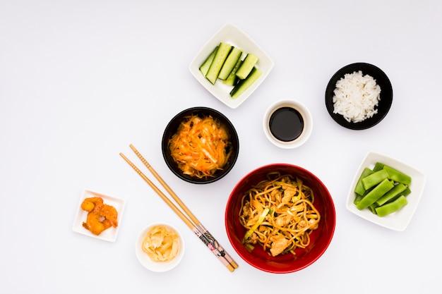 Cibo asiatico delizioso con ingredienti disposti su sfondo bianco