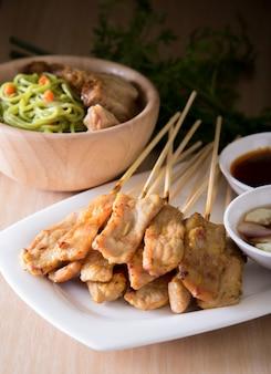 Cibo asiatico - satin di maiale con salsa di arachidi