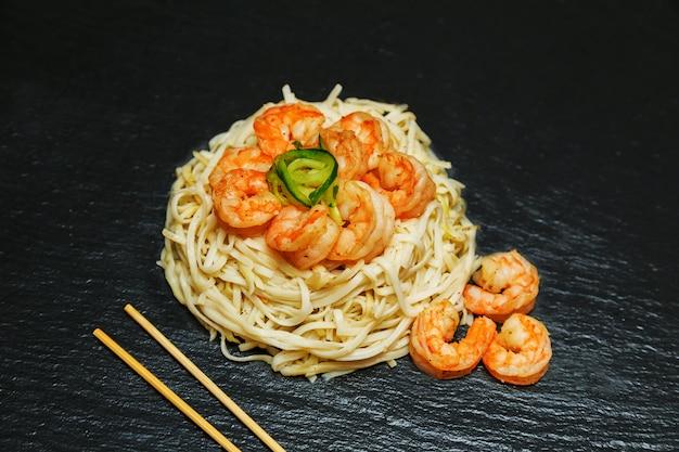Cibo asiatico: spaghetti di riso con gamberetti e verdure close-up o