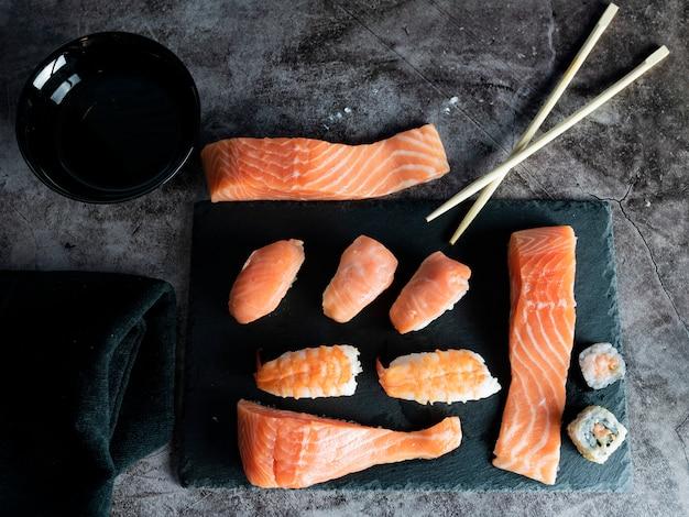 Cibo asiatico su spazio nero, sushi, salmone, soia, bacchette, piatto