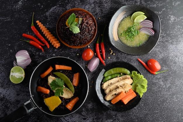 Cibo assortito e piatti di verdure, carne e pesce su un tavolo di pietra nera. vista dall'alto.