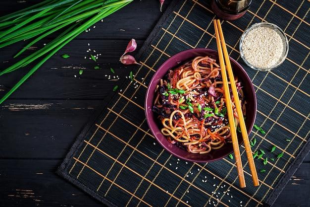 Cibo cinese. tagliatelle fritte vegane con cavolo rosso e carota in una ciotola su un fondo di legno nero. pasto di cucina asiatica. vista dall'alto