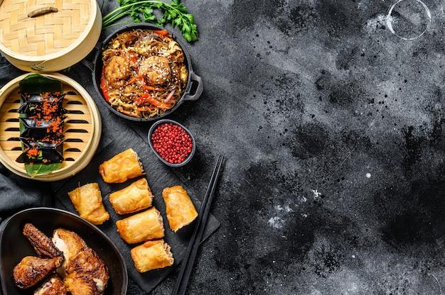 Cibo cinese. tagliatelle, gnocchi, pollo fritto, dim sum, involtini primavera. set di cucina cinese. sfondo nero. vista dall'alto. copia spazio