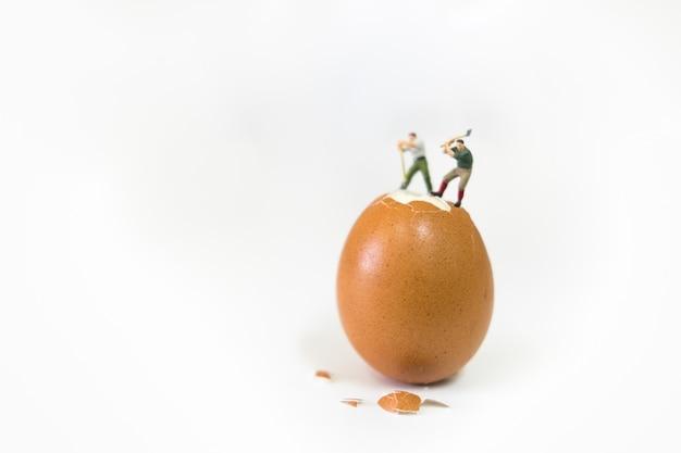Cibo, concetto di business. lavoratore di due figure in miniatura che lavora all'uovo marrone per rompere il guscio d'uovo.