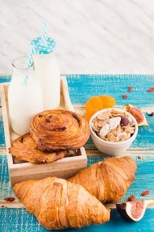 Cibo cotto con bottiglie di latte; ciotola di corn flakes fette di frutta fichi e albicocca secca sulla scrivania in legno