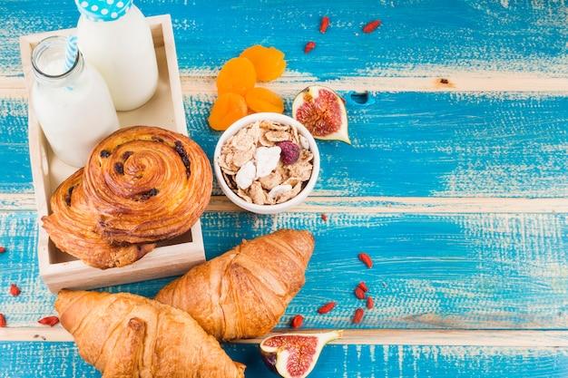 Cibo cotto con bottiglie di latte; fiocchi di mais; fichi e albicocche secche su tavola di legno blu