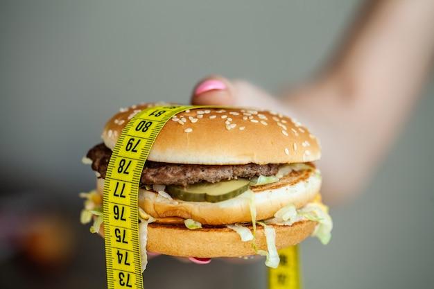 Cibo dannoso. la scelta tra cibo dannoso e sport. bella ragazza a dieta. il concetto di bellezza e salute.