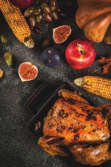 Cibo del giorno del ringraziamento. pollo intero arrosto o tacchino con frutta e verdura autunnale: mais, zucca, torta di zucca, fichi, mele, su grigio scuro, vista dall'alto