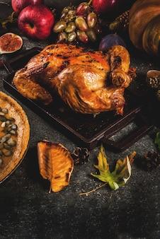 Cibo del giorno del ringraziamento. pollo intero arrosto o tacchino con frutta e verdura autunnale: mais, zucca, torta di zucca, fichi, mele, su grigio scuro,