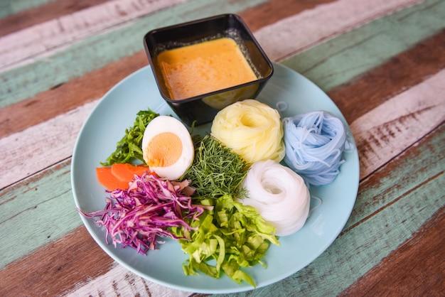 Cibo delizioso e delizioso cibo tailandese. tagliatella di riso vermicelli di riso colorati o tailandesi e salsa di minestra di curry di granchio di pesce con verdure sul tavolo in legno piatto
