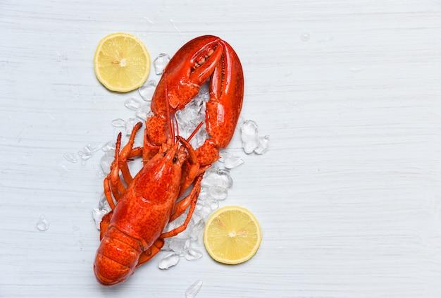 Cibo dell'aragosta sul gamberetto del pesce del ghiaccio con il limone sulla cena di legno bianca della tavola