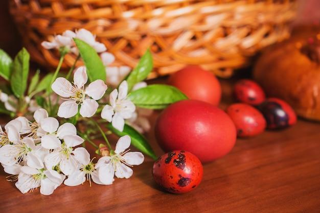 Cibo di pasqua sul tavolo. pollo colorato e uovo di quaglia. fiori contro il cestino. panorama tradizionale di vacanza in chiesa. pane pasquale. prodotti da forno freschi. cibo salutare. vacanze di primavera. inquadratura panoramica. uovo rosso