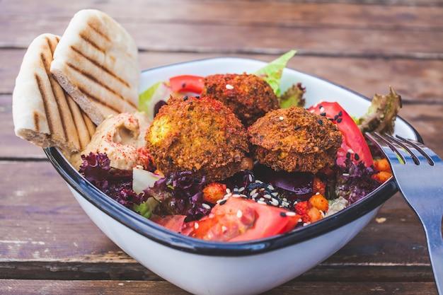 Cibo di strada israeliano. insalata di falafel con hummus, barbabietola e verdure in ciotola in un ristorante.