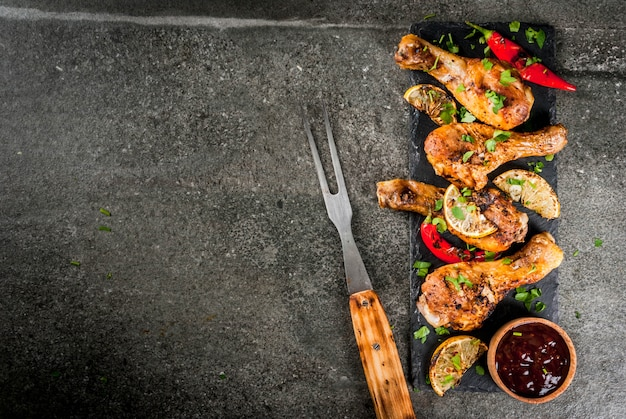 Cibo estivo. idee per barbecue, grigliate. cosce di pollo, ali grigliate, fritte sul fuoco. con peperoncino piccante, salsa al limone e barbecue. tavolo in pietra scura. copia spazio vista dall'alto