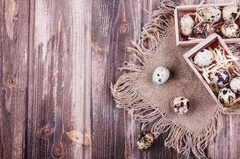 Cibo fresco e sano, proteine. Le uova di quaglia in scatola di legno stanno sul tavolo rustico