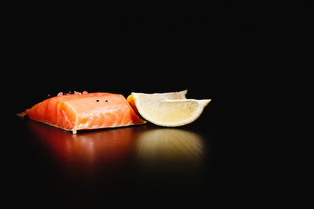 Cibo fresco, gustoso e sano salmone rosso e limone su sfondo nero isolato