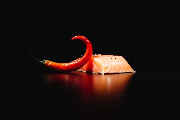 Cibo fresco, gustoso e sano salmone rosso e peperoncino su sfondo nero isolato