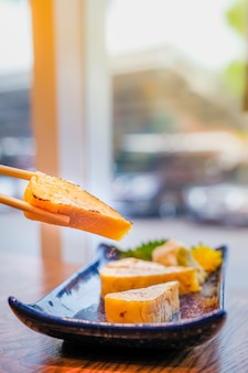 Cibo giapponese, focus su un pezzo di tamago o frittata arrotolata alla griglia che è stata raccolta da bacchette e altri pezzi in un piccolo piatto blu sul tavolo di legno