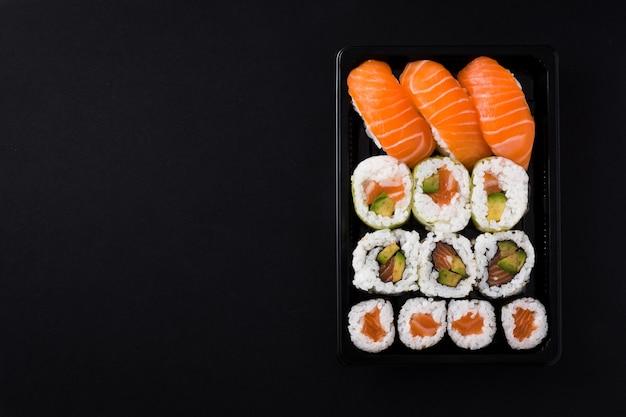Cibo giapponese: maki e nigiri sushi impostato su vista dall'alto nero, copia spazio