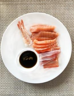 Cibo giapponese, sashimi di pesce: gamberi dolci, salmone, tonno e polpa di granchio con salsa nel whi