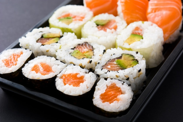 Cibo giapponese: sushi maki e nigiri incastonati sul nero. avvicinamento