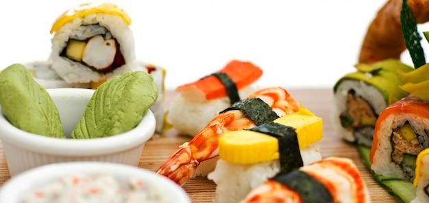 Cibo giapponese - sushi, sashimi, rotoli su una tavola di legno. isolato