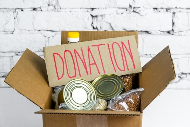 Cibo in scatola di donazione di cartone. scorte anticrisi di beni essenziali per il periodo di isolamento in quarantena. consegna del cibo, coronavirus.