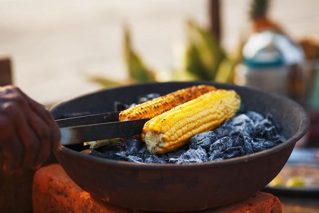 Cibo indiano sulla spiaggia - i carboni vengono arrostiti con pannocchie di mais fresche.