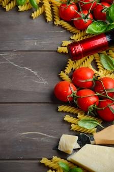 Cibo italiano, fusilli crudo, pomodoro, basilico, formaggio e vino sul tavolo di legno.