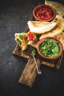 Cibo latino americano, messicano, cileno. empanadas di pasticceria tradizionale al forno con carne di manzo, due salse piccanti