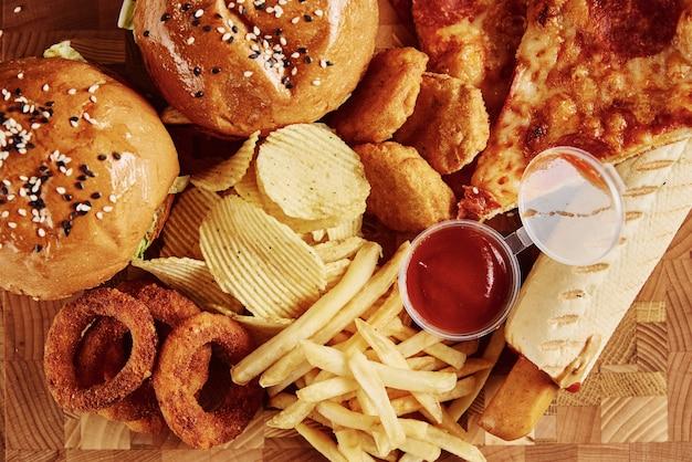 Cibo malsano e spazzatura. diversi tipi di fast food sul tavolo, primi piani