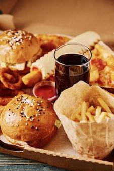 Cibo malsano e spazzatura. diversi tipi di fast food sul tavolo
