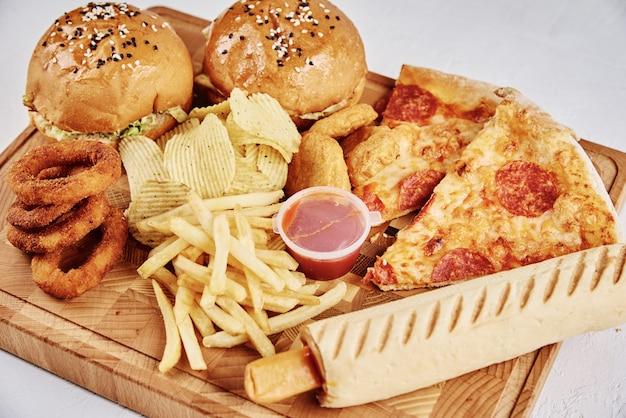 Cibo malsano e spazzatura. tipi differenti di alimenti a rapida preparazione sulla tavola, primo piano