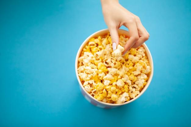 Cibo. mano della donna che prende popcorn dal secchio. secchio di popcorn su blu. cinema