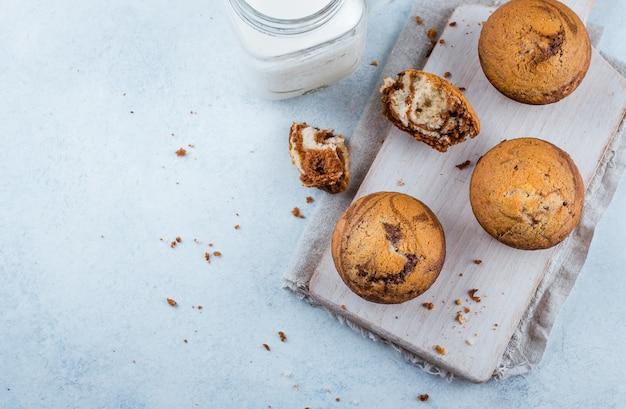Cibo. muffin alla vaniglia casalinghi del cioccolato zuccherato da due tipi di impasti con il barattolo di latte del muratore sopra sul bordo di legno sul tavolo della pietra blu
