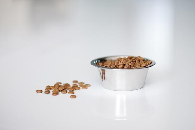 Cibo per gatti a secco in un piatto rotondo d'argento su un pavimento bianco in cucina. copia spazio