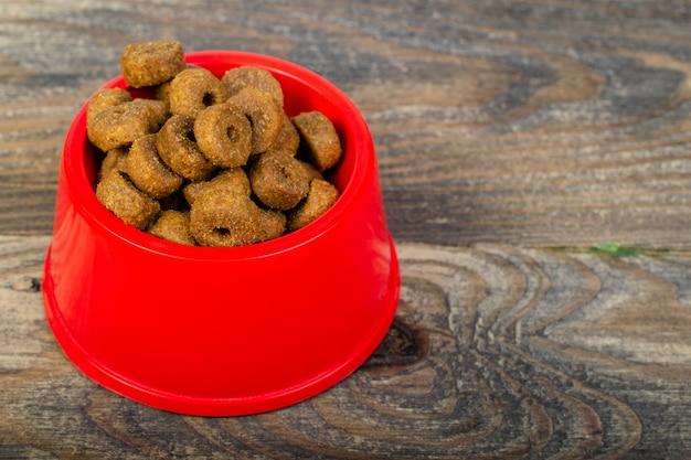 Cibo per gatti croccante secco in ciotola di plastica rossa, che si trova sul pavimento o sul tavolo di legno.