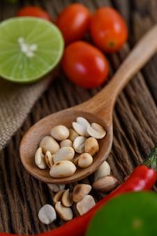Cibo piccante in stile tailandese, concetto di cibo som tum, decorazione di oggetti di scena aglio, limone, pomodori, peperoncino e arachidi sul cucchiaio di legno sul tavolo di legno