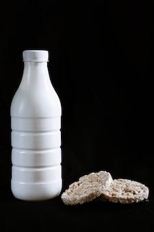 Cibo salutare. bottiglia di kefir e panini su sfondo nero. oggetti bianchi su uno sfondo isolato. dieta sana. pane integrale e kefir a basso contenuto calorico
