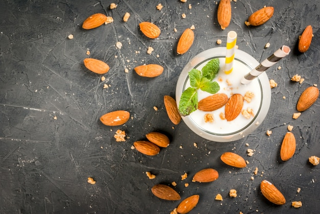 Cibo salutare. colazione dietetica o merenda. frullati bianchi a base di yogurt, banana e noci di mandorle. decorato con la menta. su un tavolo di cemento scuro con ingredienti, cannucce a strisce. vista dall'alto