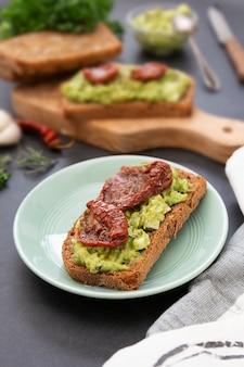 Cibo salutare. pane di segale con guakomole, pasta di avocado e pomodori secchi, sul tagliere di legno. toast all'avocado.