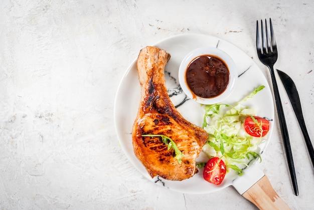 Cibo salutare. porzione di insalata fresca con pomodori, rucola, foglie di lattuga, cavolo e maiale alla griglia o cotoletta di vitello su osso, salsa barbecue. sul piatto di marmo bianco, tavolo bianco. vista dall'alto